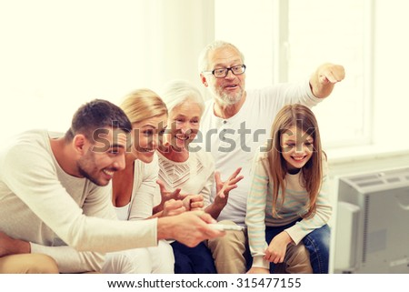 family, happiness, generation and people concept - happy family sitting on sofa and watching tv at home - stock photo