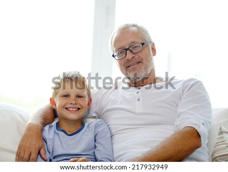 family, happiness, generation and people concept - smiling grandfather with grandson sitting on couch at home
