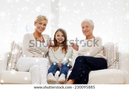 family, happiness, generation and people concept - smiling mother, daughter and grandmother sitting on couch at home