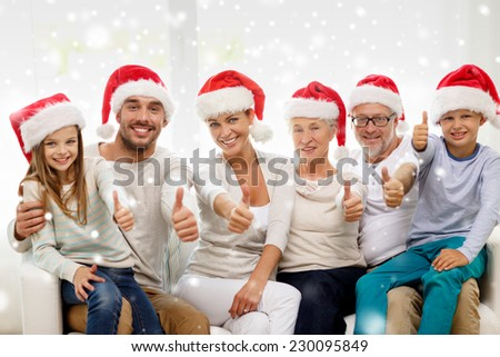 family, happiness, generation, holidays and people concept - happy family in santa helper hats sitting on couch and showing thumbs up gesture at home - stock photo