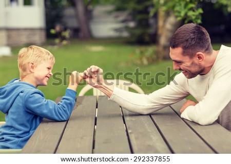 family, happiness, generation, home and people concept - happy father and son doing arm wrestling outdoors - stock photo