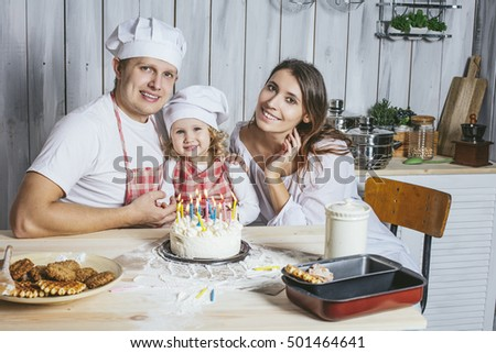 Family, happy daughter with mom and dad at home in the kitchen laugh and lit the candles on the birthday cake, together, with love