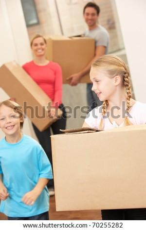 Family happy on moving day carrying cardboard boxes - stock photo