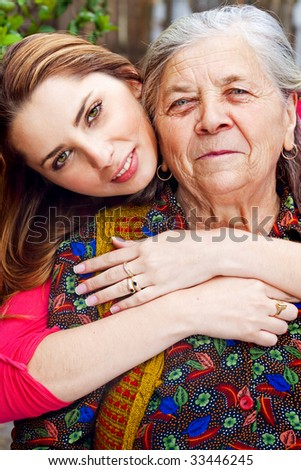 Family - happy young woman with her grandmother - stock photo