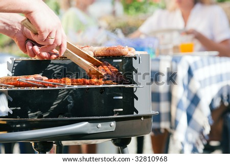 Family having a barbecue in the garden - focus on cooking in the foreground