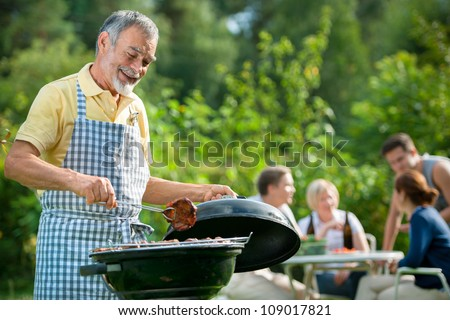 Family having a barbecue party in their garden in summer - stock photo