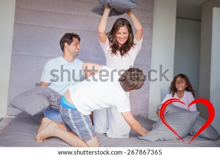 Family having a pillow fight on the bed against heart - stock photo