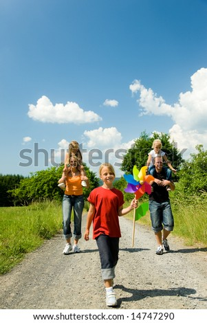 Family having a walk down a path on a sunny day under a perfect blue sky (focus is only on the girl in front!) - stock photo