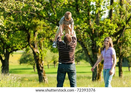 Family having a walk outdoors in summer, throwing their little son in the air in a playful way - stock photo