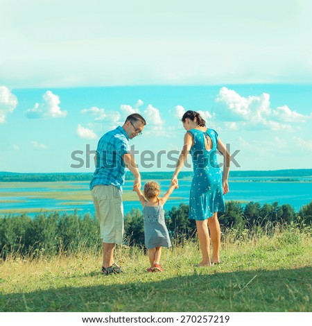 Family having a walk outdoors, throwing their little child in the air in a playful way. Portrait of a happy family. - stock photo