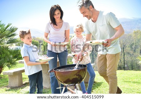 Family having barbecue lunch in garden - stock photo