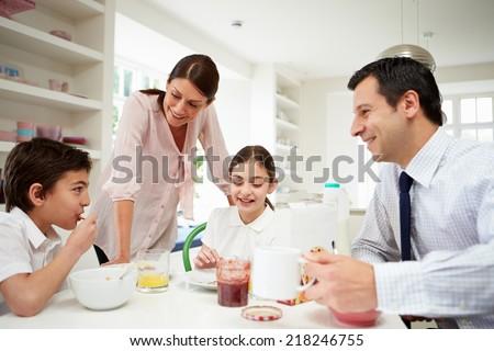 Family Having Breakfast Before Husband Goes To Work - stock photo