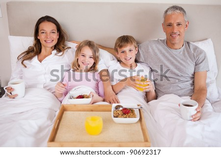 Family having breakfast in a bedroom while looking at the camera