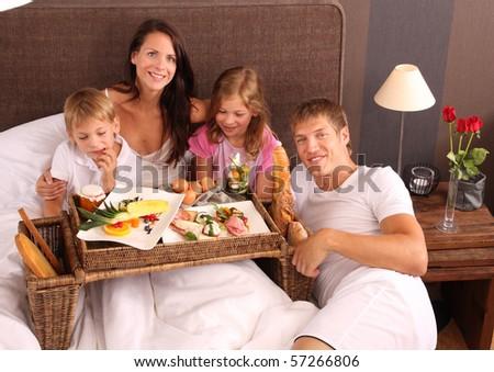 family having breakfast in bed - stock photo