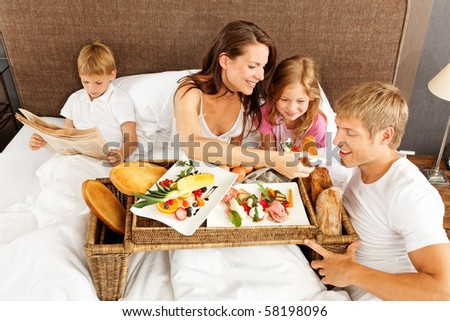 family having breakfast in bed - boy reading newspaper - stock photo