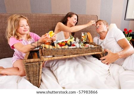 family having breakfast in bed - feeding each other - stock photo
