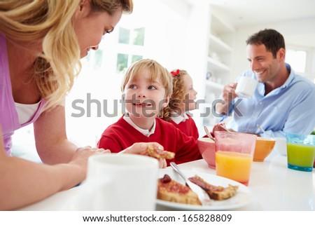 Family Having Breakfast In Kitchen Before School - stock photo
