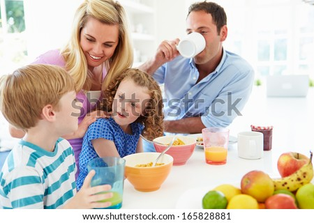 Family Having Breakfast In Kitchen Together - stock photo