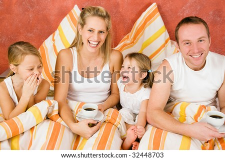 Family having breakfast in their bed in the morning - stock photo