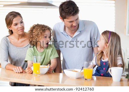 Family having breakfast in their kitchen - stock photo