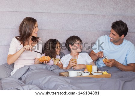 Family having breakfast together in bed - stock photo
