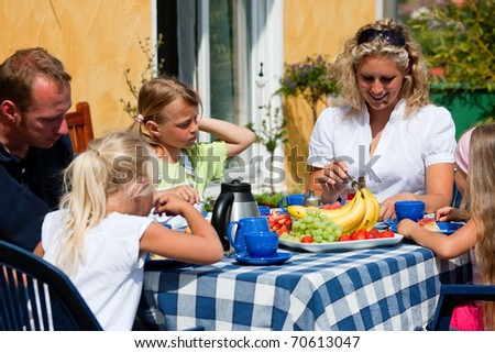 Family having coffee in their garden, they are eating fruits and strawberry cake - stock photo