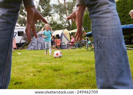 Family Having Football Match On Camping Holiday   - stock photo