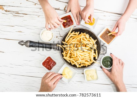 Family having french fries with different sauces for dinner. Top view.