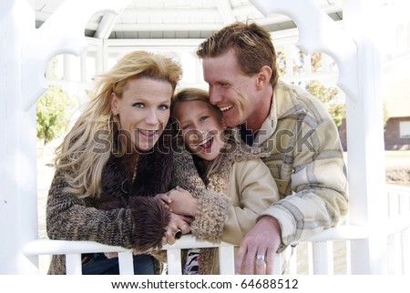 Family having fun at the park laughing and playing - stock photo