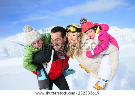 Family having fun at the top of snowy mountain - stock photo