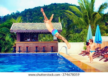 family having fun in pool on tropical vacation - stock photo