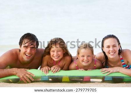 Family Having Fun In Sea On Airbed - stock photo