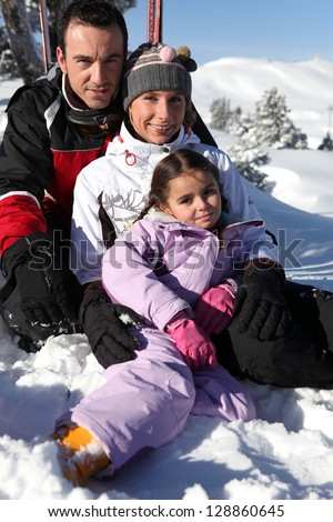 Family having fun in the snow - stock photo