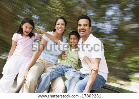 Family having fun on spinning roundabout