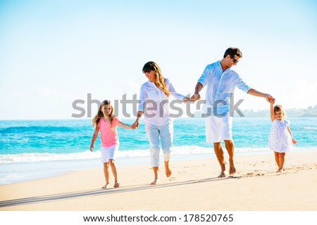 Family having fun on the beach - stock photo