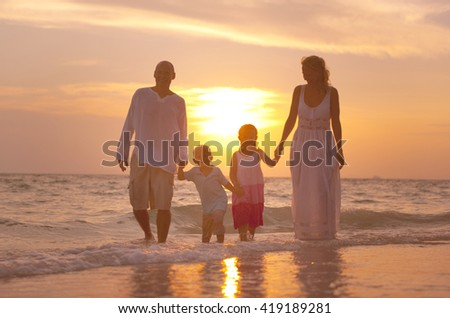Family having fun on vacation with perfect sunset - stock photo
