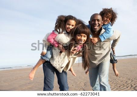 Family Having Fun On Winter Beach - stock photo
