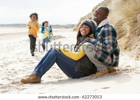 Family Having Fun On Winter Beach