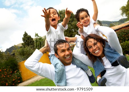 family having fun outdoors looking very happy - stock photo