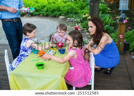 Family having fun painting and decorating eggs outside.  Mother and father help children color dye their Easter eggs during the springtime in a garden setting.  Part of a series.  - stock photo