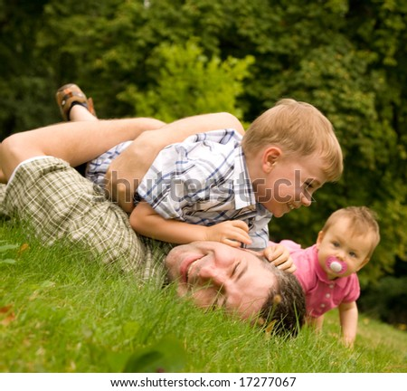 Family having fun together on grass, rural background. Father wrestling with young son as baby sister watches. - stock photo