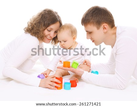 Family having fun together, parents and baby playing with colorful toys - stock photo