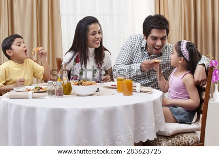 Family having fun while eating pizza together at restaurant - stock photo