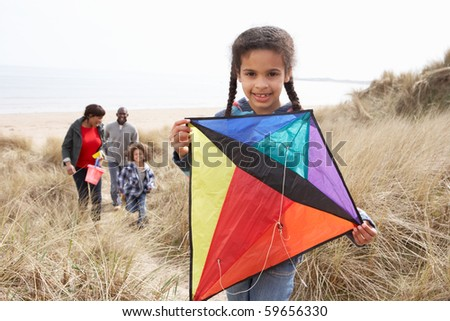 Family Having Fun With Kite In Sand Dunes - stock photo