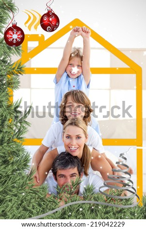 Family having fun with yellow drawing house against twinkling stars - stock photo