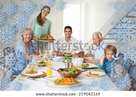 Family having meal at dining table against snowflake frame
