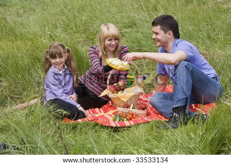 Family having picnic in park. Parents and child on picnic in the forest. Mother, father and daughter relaxing. Wife is giving husband sandwich. - stock photo