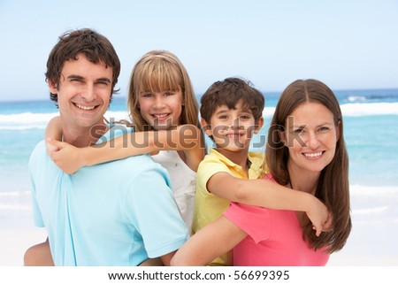 Family Having Piggyback Fun On Beach Holiday - stock photo
