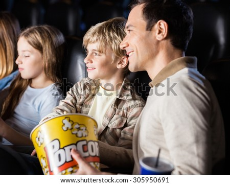 Family having popcorn while watching movie in cinema theater - stock photo