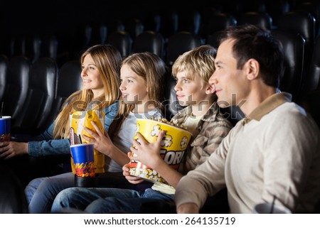 Family having snacks while watching film in movie theater